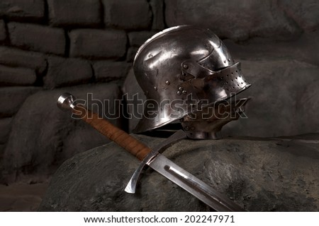 Closeup of knight armor helmet and sword on the dark stone wall background - stock photo