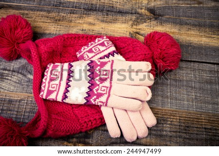 Closeup of knitted winter gloves and cap on wooden board - stock photo