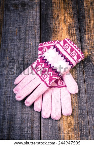 Closeup of knitted winter gloves isolated on wooden board - stock photo
