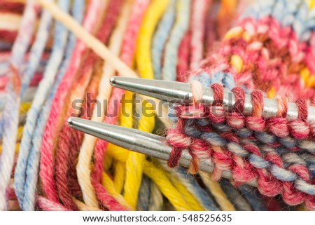 Closeup of knitting needles with multicolored wool
