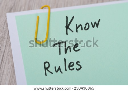 Closeup of Know The Rules ! written on green paper note with paperclip - stock photo