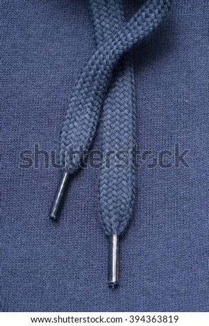 Closeup of laces in plastic aglets on blue cotton fabric. - stock photo