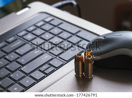 Closeup of laptop computer, mouse, and gun bullets, representing the concept of cyber attacks. - stock photo
