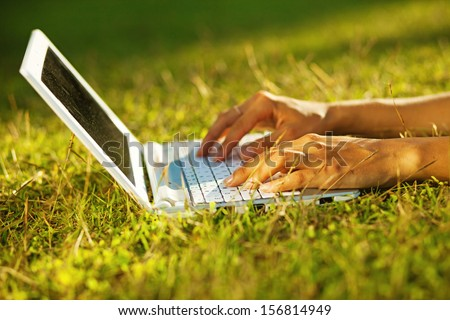 closeup of laptop on a grass (soft focus on fingers) - stock photo