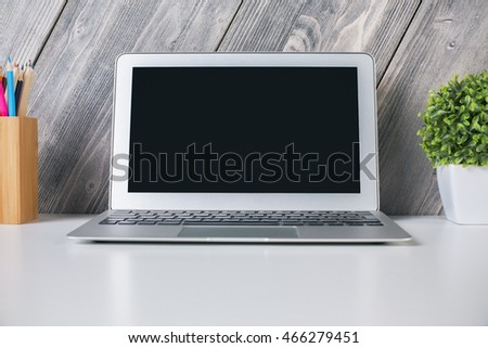 Closeup of laptop with blank screen on light desktop with decorative plant and pencils. Wooden plank background. Mock up