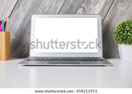 Closeup of laptop with white screen on light desktop with decorative plant and pencils. Wooden plank background. Mock up