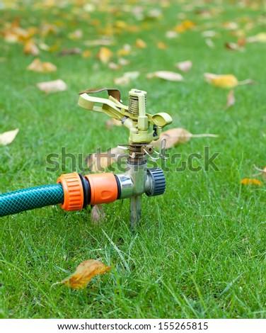 closeup of lawn sprinkler over green wet grass in autumn garden - stock photo