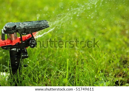 closeup of lawn sprinkler with copy-space - stock photo