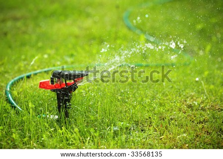 closeup of lawn sprinkler with copyspace - stock photo