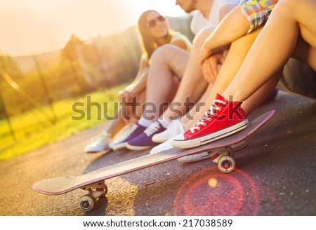 Closeup of legs and sneakers of young people on skateboard - stock photo