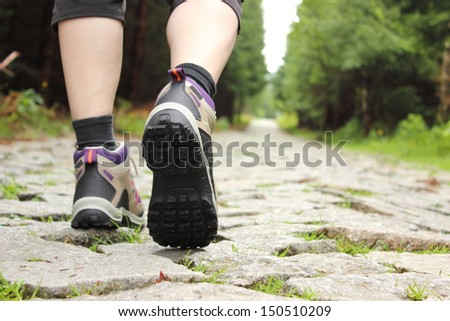 Closeup of legs of a woman in hiking boots in outdoor action