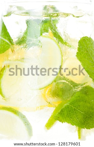 Closeup of lemonade in a pitcher with ice and lemon and lime slices - stock photo