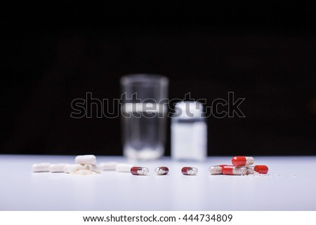 Closeup of light desktop with different pills and blurry medicine bottle and water glass on dark background - stock photo