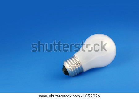 Closeup of lightbulb on blue background - stock photo