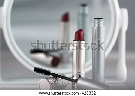 Closeup of lipstick and mascara with a blurred reflection in a makeup mirror.  Could be used as a metaphor for beauty. - stock photo