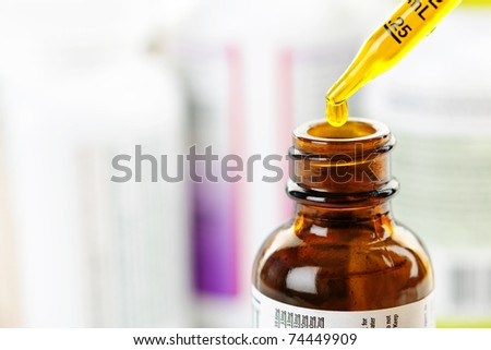 Closeup of liquid medicine in glass dropper and bottle
