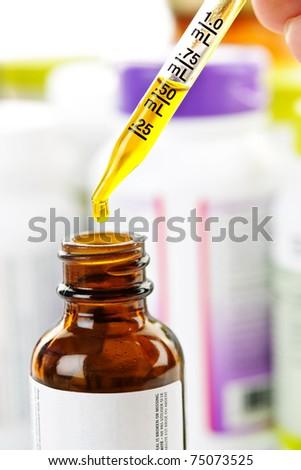 Closeup of liquid medicine in glass dropper and bottle - stock photo
