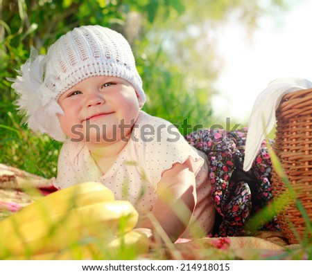 Closeup of little baby girl with basket with fruit - stock photo