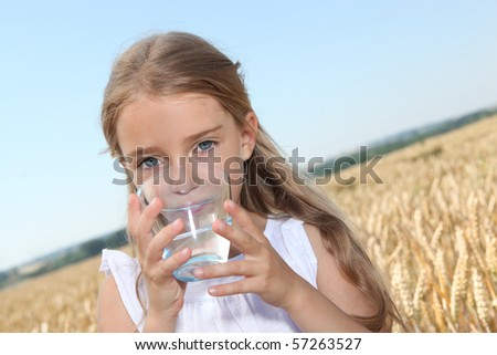 Closeup of little blonde girl drinking water - stock photo