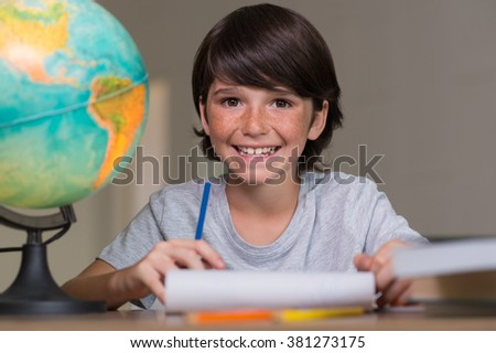 Closeup of little boy doing homework beside globe of earth. Portrait of happy young boy smiling and looking at camera sitting at desk. Cheerful cute boy doing his homework at desk. - stock photo