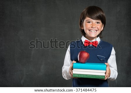 Closeup of little boy holding stack of books and apple. Happy schoolboy smiling and looking at camera. Cheerful child holding books with red apple standing isolated on blackboard with copy space. - stock photo