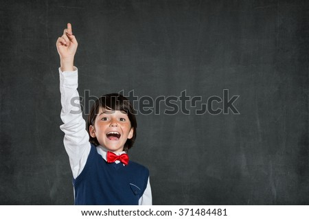 Closeup of little boy with raised hand isolated on blackboard. Schoolboy pointing high his index finger. Cheerful cute boy with raised hand standing against black background. - stock photo