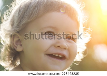 Closeup of little cute happy boy with blonde curly hair smiling sunny day outdoor on natural background, horizontal picture - stock photo