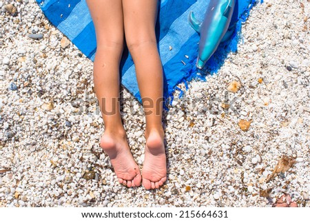 Closeup of little girl legs on tropical beach with pebbles - stock photo