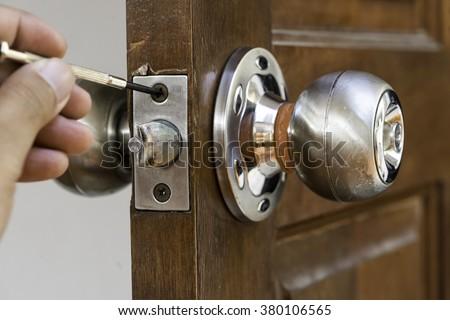 closeup of locksmith on old wood door , repair - stock photo