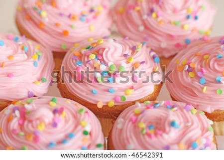 Closeup of lots of pretty pink cupcakes. - stock photo