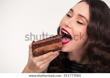 Closeup of lovely cute curly girl with retro hairstyle eating piece of chocolate birthday cake with candle over white background - stock photo