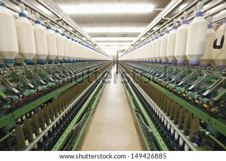 Closeup of machinery part at spinning factory - stock photo