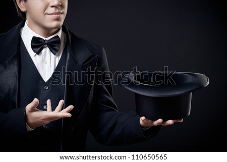 closeup of magician showing tricks with top hat isolated on dark background - stock photo