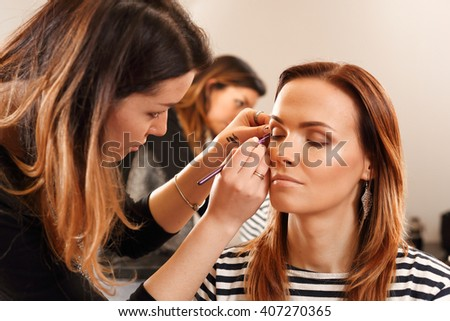 Closeup of makeup artist apply eyeliner on the clients eyes. The process of working professional makeup. Master of makeup draws brush eyes of the girl. - stock photo