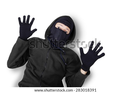 Closeup of male burglar wearing black mask and jacket, shot in studio with expression of caught and surrender - stock photo
