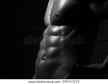 Closeup of male cool strong naked abdomen with strong abs and 6 pack muscles and beautiful strong topless breast of sexy young man athlete closeup black and white studio on dark background - stock photo