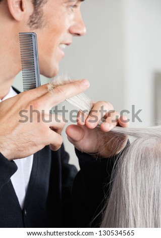 Closeup of male hairdresser cutting senior woman's hair at hair salon - stock photo