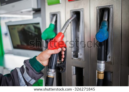 Closeup of male hand holding gas pump nozzle at gas station. - stock photo