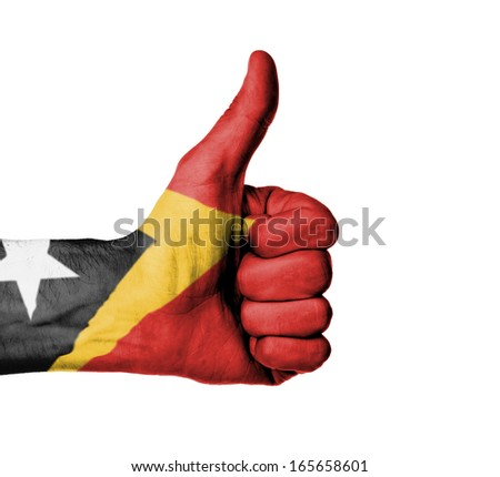 Closeup of male hand showing thumbs up sign, flag of East Timor - stock photo