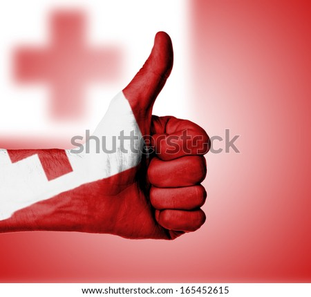 Closeup of male hand showing thumbs up sign, flag of Tonga - stock photo