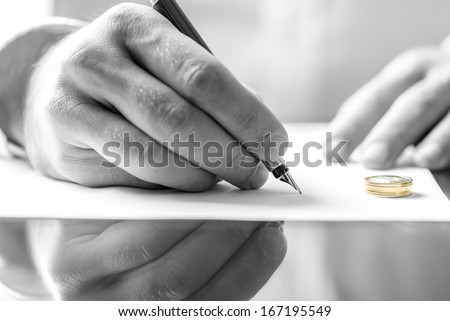 Closeup of male hand signing divorce papers. - stock photo