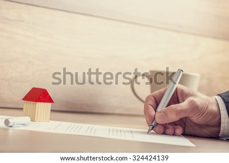 Closeup of male hand signing insurance papers, contract of house sale or mortgage documents with fountain pen, wooden toy house sitting on paperwork. - stock photo