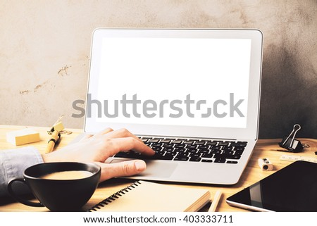 Closeup of male hand typing on blank white laptop keyboard on wooden desk with coffee and office tools. Mock up - stock photo