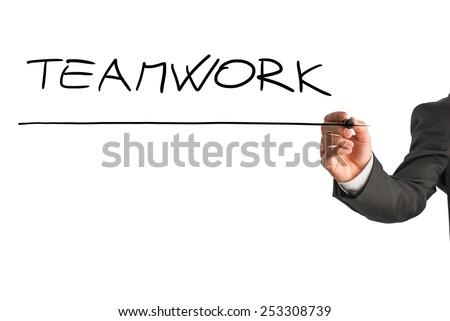 Closeup of male hand writing the word Teamwork on white virtual screen. - stock photo