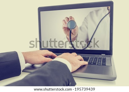 Closeup of male hands browsing the internet seeking for online medical advice, retro effect faded look.