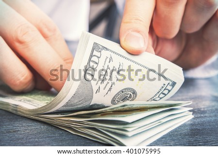 Closeup of male hands counting hundred-dollar bills on darl wooden table - stock photo
