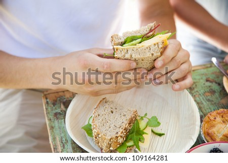 Closeup of male hands holding a healthy sandwich with cheese and lettuce