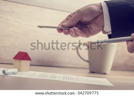 Closeup of male hands holding a house key and a pen over a contract of house sale lying on wooden desk with house miniature and coffee cup in background. - stock photo