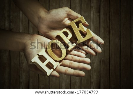 Closeup of male hands holding a word of HOPE - stock photo