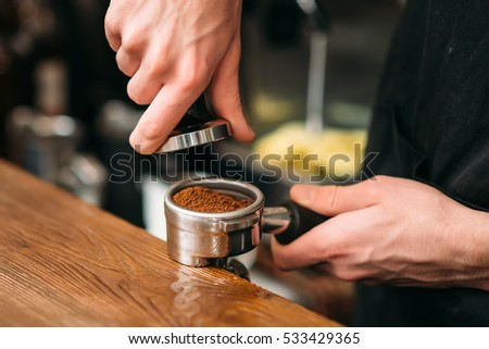 Closeup of male hands making coffee.